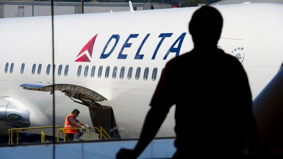 A passenger looks out towards a Delta Air Lines Inc.