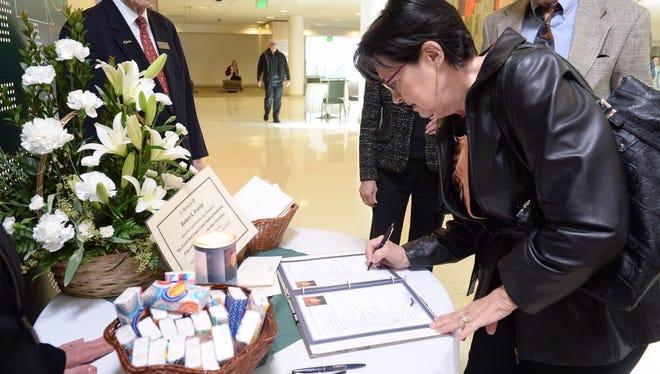 Debbie Scalva signs the guestbook before entering Bob Everitt's memorial service Tuesday, Feb. 23 at CSU.