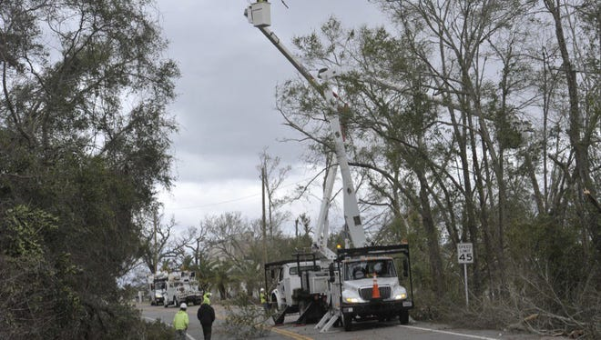 Gulf Power crews work along Scenic Highway. Retirees in the community disagree with the utility's proposal to the state for a rate increase.