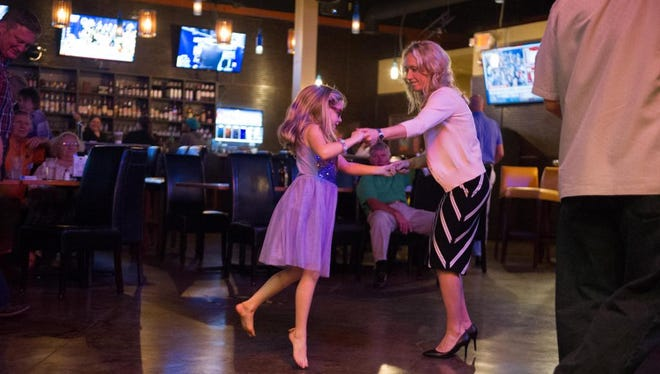 Miranda DeBruhl dances with her daughter following her victory Tuesday.