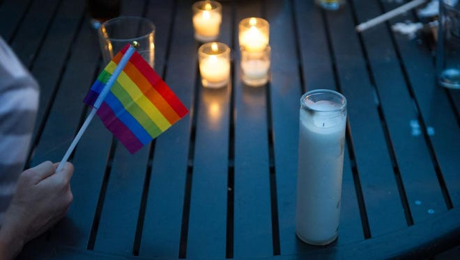 Hundreds gathered outside of O. Henry's bar on Haywood St. to join a candlelight vigil for victims of the massacre at the Pulse nightclub in Orlando, Fl.