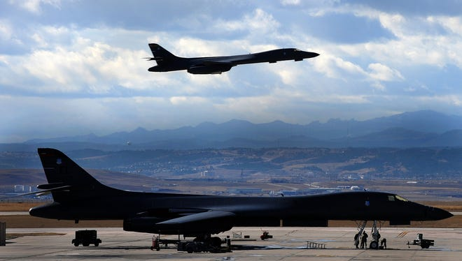 U.S. Airmen conduct maintenance on a B-1B Lancer aircraft as another B-1 flies over head Nov. 2, 2009, at Ellsworth Air Force Base, S.D. The B-1B can rapidly deliver massive quantities of precision and non-precision weapons against any adversary, anywhere in the world. (DoD photo by Airman 1st Class Joshua J. Seybert, U.S. Air Force/Released)