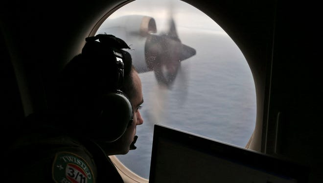 Flight officer Rayan Gharazeddine scans the water in the southern Indian Ocean off Australia from a Royal Australian Air Force AP-3C Orion during a search for the missing Malaysia Airlines Flight MH370.