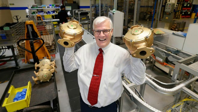 Richard A. Meeusen, chairman, president and chief executive officer of Badger Meter holds a couple of commercial meters made of brass and copper in the large meter plant at the company headquarters at 4545 West Brown Deer Rd. in Brown Deer on Monday, May 8, 2017. The 62-year-old head of the company, which makes water meters and other flow measuring device, is known for his irreverent and unfiltered management style. Meeusen is reinventing his company and moving it into high tech. Sales and earnings and stock price are at record levels. And he's leading the water-technology efforts in the region, which many laud as the fastest growing and most effective economic development initiative in the metro region in anyone's memory.