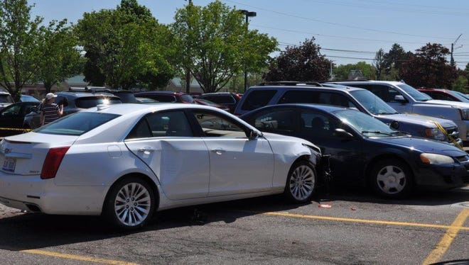 Bloomfield Township Police say the driver of the Cadillac CTS struck a pedestrian before crashing into two parked cars in a Kroger parking lot.