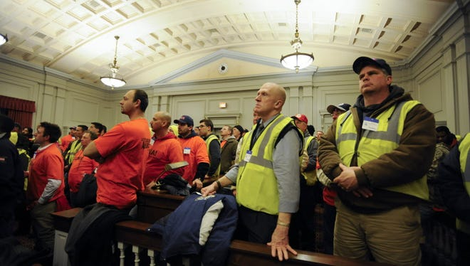 In this 2015 file photo, Glen Horishny, right, and John Wood, left, of Local 825 of the International Union of Operating Engineers, listen to members of ForwardNJ as they urge for action from state lawmakers on funding for the Transportation Trust Fund.