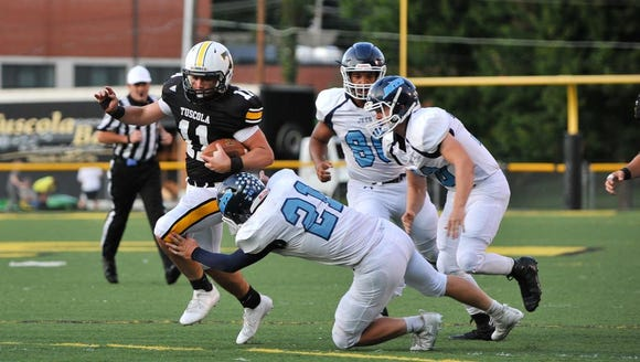 Enka's Chase Bennett (21) tries to take down Tuscola's