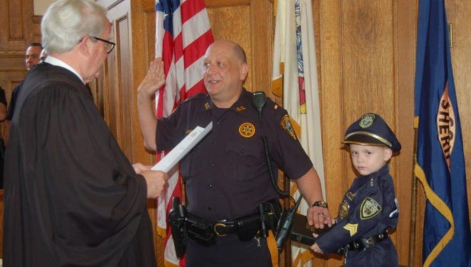 Lt. Michael DiGuilio is sworn in by Superior Court Judge Paul Armstrong, as Trenton Rhea holds the Bible for his grandfather.