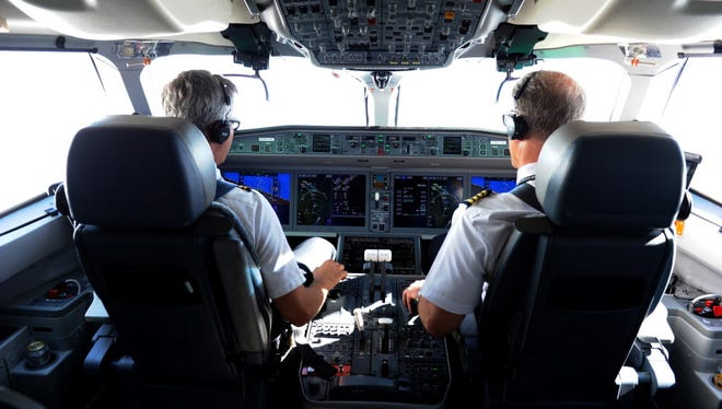 Pilots sit in the cockpit June 29, 2016, as members of the media fly on board a Bombardier CS100, made by Canadian plane maker Bombardier, north of Montreal.