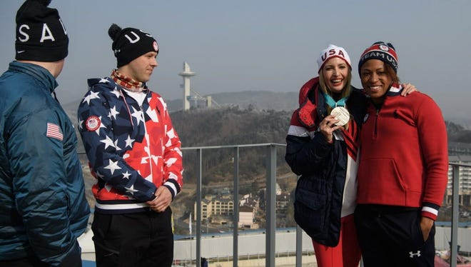 President Donald Trump's daughter and senior White House adviser Ivanka Trump (2nd R) poses for a photo on a balcony of the VIP tent at the Olympic sliding center with US Army Luge athletes Taylor Morris (L) and Matt Mortensen (2nd L), and US womens bobsled silver medalist Lauren Gibbs.