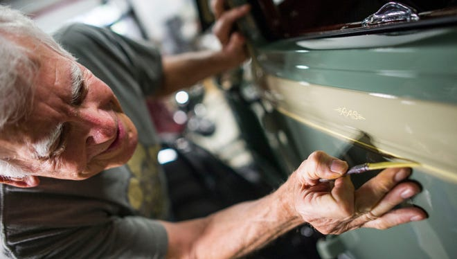 Alex Olivera finishes a line on a car at a shop in Naples on Wednesday, March 28, 2018.