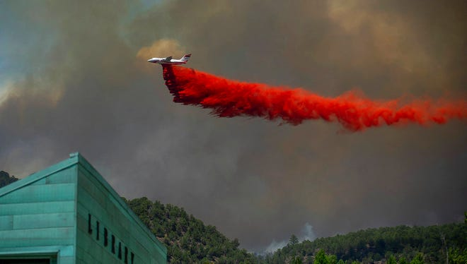 A plane drops fire retardant on homes in the area of Basalt, Colo., Wednesday, July 4, 2018, during the Lake Christine Fire.