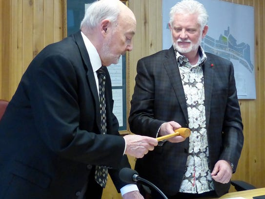 Former mayor Tom Battin hands over the gavel to new
