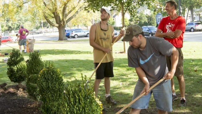 Jim Brickham, forefront, rakes out the dirt around newly planted bushes Saturday, Sept. 23, 2017, at South Park Middle School as part of Project CURB.