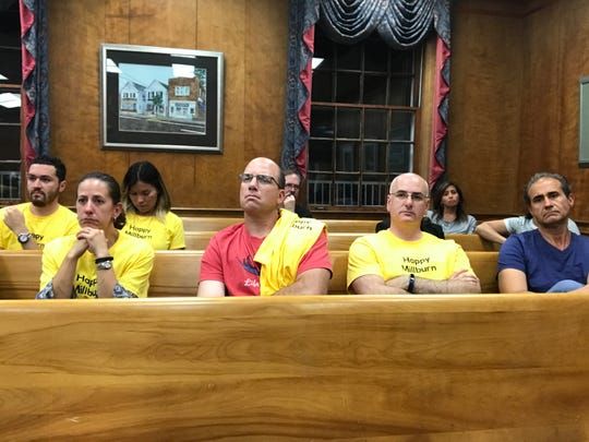 "Members of the audience sport ""Happy Millburn"" T-shirts during the Tuesday, Sept. 19, 2017 Millburn Township Committee session."