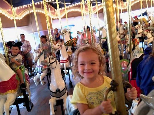 Isabella enjoys riding the carousel at Disney World's Magic Kingdom.