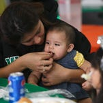 Carmen Castro feeds bits of turkey to her niece, Sofia Aguado at the Red Rock Canyon School's annual free community Thanksgiving dinner Thursday, Nov. 27, 2014.