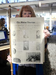 """Wen Livingston, a senior Librarian at the downtown branch of the West Florida Public Library holds up a restored copy newpspaper, The Molino Advertiser, from 1915, which will be incorporated into the upcoming traveling Smithsonian exhibit, """"The Way We Worked,"""" in Molino."""