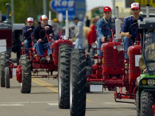Antique tractors make their way down Main Street in