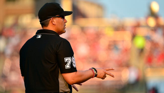 Umpire Manny Gonzalez signals two outs during the game between the Rockies and Cardinals at Busch Stadium.