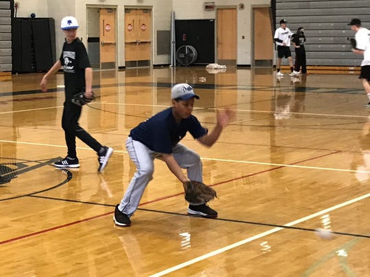 A young infielder gets down in his stance to receive a ground ball during the clinic at Plymouth High School.