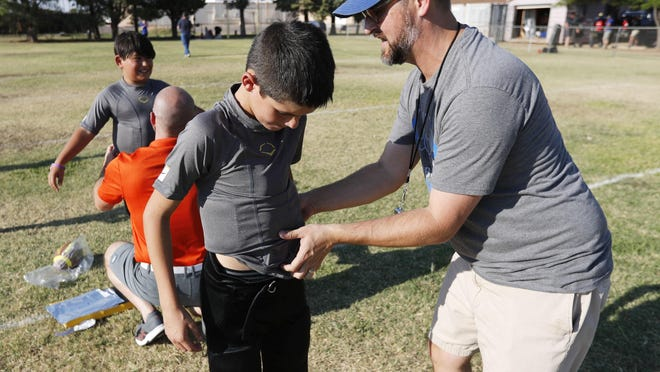 Lubbock Titan coach Scott Bivens fits Bryan Morris with abdominal pads. The Lubbock Homeschool Christian Athletic Association's Lubbock Titan football team received protective abdominal pads fitted by the Taylor Haugenn Foundation's YESS Program in memory of Taylor Haugenn, who died after getting an abdominal injury during a game. The he pads were fitted on the football field behind St. John Newman Catholic Church Tuesday evening.