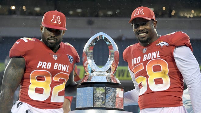 AFC tight end Delanie Walker of the Tennessee Titans (82) and outside linebacker Von Miller of the Denver Broncos (58) pose with the Pro Bowl MVP trophy.