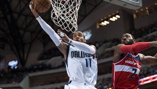 Monta Ellis drives to the basket past Wizards guard John Wall.