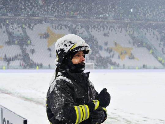 A firefighter watches the pitch of the Allianz Stadium in Turin, Italy, Sunday, Feb. 25, 2018. Snowfall has prompted the Serie A match between six-time defending champion Juventus and Atalanta to be postponed. Fans filled the Allianz Stadium shortly before the scheduled kickoff Sunday but when the referee could not roll the ball on the snow-covered pitch, the game was quickly called off. (Alessandro Di Marco/ANSA via AP)
