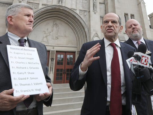 Mitchell Garabedian, Boston attorney, center, flanked by Robert Hoatson, former priest and founder of Road to Recovery, a victims' support organization, left, and James Faluszczak, survivor of abuse and former priest, right, hold a press conference on Diocese of Rochester priests accused of abuse outside the Diocese of Rochester.