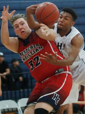 Desert Hot Springs High School's Isiaha Davis, at right, tries to control the ball from Spencer Doherty of Hesperia Christian High School at Desert Hot Springs on February 16, 2018.