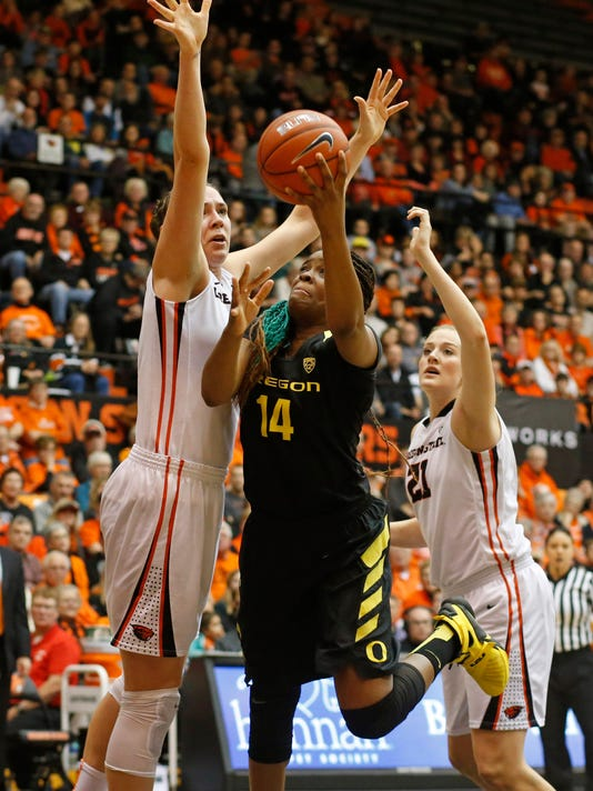 Oregon's Jillian Alleyne, center, tries to drive past Oregon State's Ruth Hamblin, left, and Marie Gulich, right, in the first half of an NCAA college basketball game, in Corvallis, Ore., on Friday, Jan. 8, 2016. (AP Photo/Timothy J. Gonzalez)