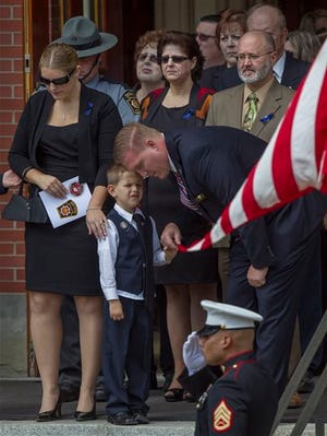 Murdered Pennsylvania State Trooper Cpl. Bryon Dickson's wife Tiffany, one of their sons, parents and family leave Saint Peter's Cathedral in Scranton, Pa. after his funeral, Thursday, Sept. 18, 2014. (AP Photo/PennLive.com, Mark Pynes)