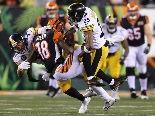 Cincinnati Bengals wide receiver A.J. Green (18) is tackled by Pittsburgh Steelers cornerback Artie Burns (25) and Pittsburgh Steelers linebacker L.J. Fort (54) in the third quarter during the Week 13 NFL game between the Pittsburgh Steelers and the Cincinnati Bengals, Monday, Dec. 4, 2017, at Paul Brown Stadium in Cincinnati. Pittsburgh won 23-20.