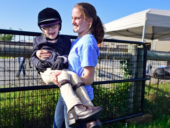 Sophia Eck prepares to ride a horse at Leg Up Farm in York County in September 2017..