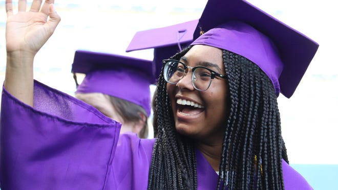 A Blue Springs High School graduate waves to family in the crowd during Saturday's commencement ceremony.