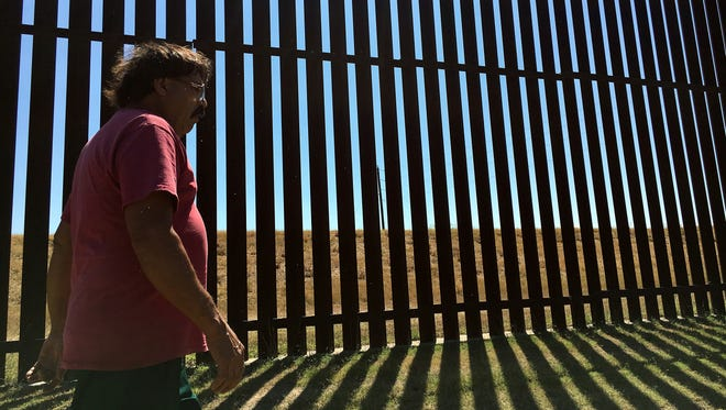 Jose Manuel Reyes walks along the border fence that is located in his backyard in Brownsville, Texas in this May photograph.
