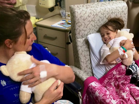 Jodi Schmidt, left, hugs a teddy bear while Natasha Fuller hugs a teddy bear and smiles Friday at Children's Hospital in Milwaukee as the two met for the first time following kidney donation and transplant surgeries Tuesday.