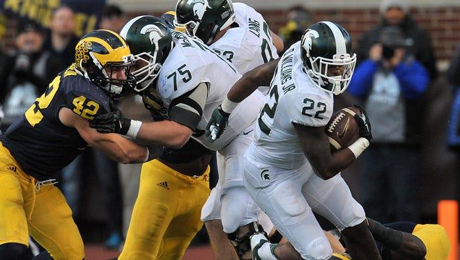 Michigan State running back Delton Williams runs through the line in the fourth quarter Saturday against Michigan.