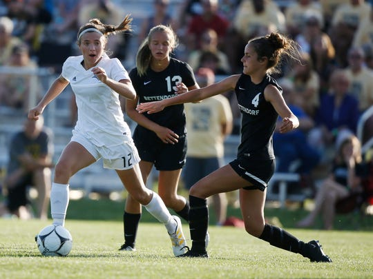 Ankeny Centennial senior Abby Yaske (12) runs the ball as Dowling Catholic junior Kate Brosnanhan (4) defends Thursday, June 8, 2017, during the 3A girls state quarterfinals at the Cownie Sports Complex in Des Moines.