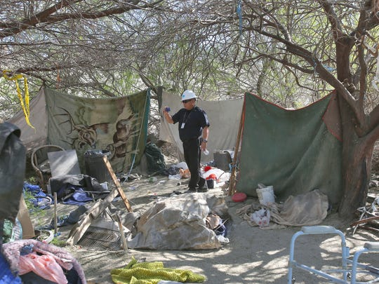 Alex Alarcon, a code enforcement officer with the city of Coachella, documents a homeless camp in the thick brush just off the Dillon on-ramp onto Hwy 86, February 29, 2016.