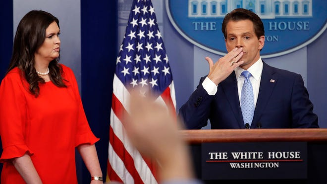 Sarah Huckabee Sanders, left, the new White House press secretary, watches as Scaramucci blows a kiss after answering questions during the press briefing on July 21, 2017.