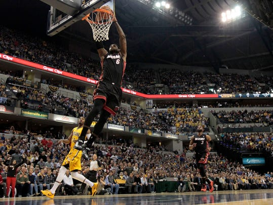 Miami Heat forward LeBron James (6) scores a break away dunk in front of Indiana Pacers forward Paul George (24) during the first half of an NBA basketball game in Indianapolis, Wednesday, March 26, 2014. (AP Photo/AJ Mast)