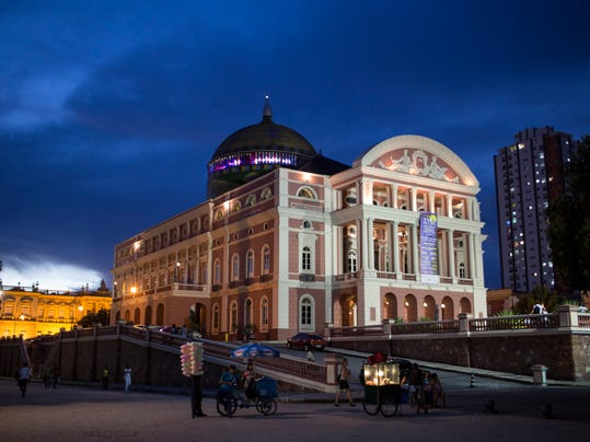This May 20, 2014 photo, the Teatro Amazonas is seen as dusk in Manaus, Brazil. The theater is the symbol of Manaus, a city carved out of the rainforest, still so remote it can only be reached by plane or boat even though it has grown to over 2 million inhabitants. (AP Photo/Felipe Dana)