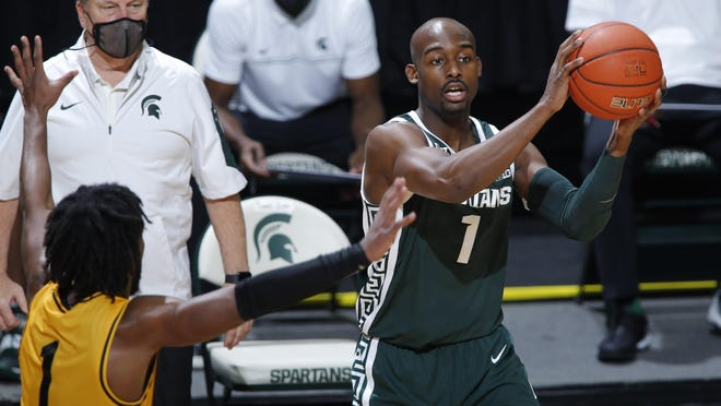 Michigan State's Joshua Langford, right, looks to pass against Oakland's Rashad Williams during the second half of an NCAA college basketball game, Sunday, Dec. 13, 2020, in East Lansing, Mich.