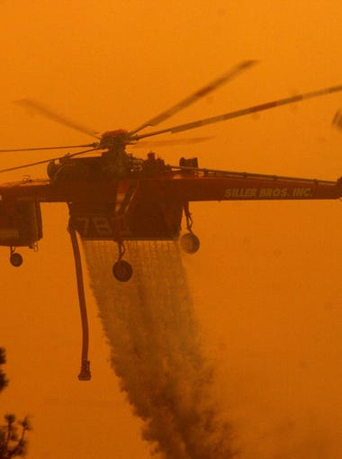 ANGORA FIRE: A helicopter releases its load of water during the Angora Fire in June 2007.