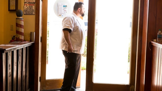 Barber Stoney Dupuis stands at the doorway of Acadiana Barber Company in River Ranch.