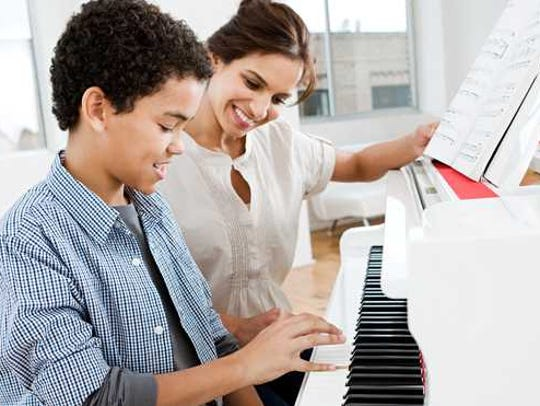 Young boy playing piano while woman looks on.