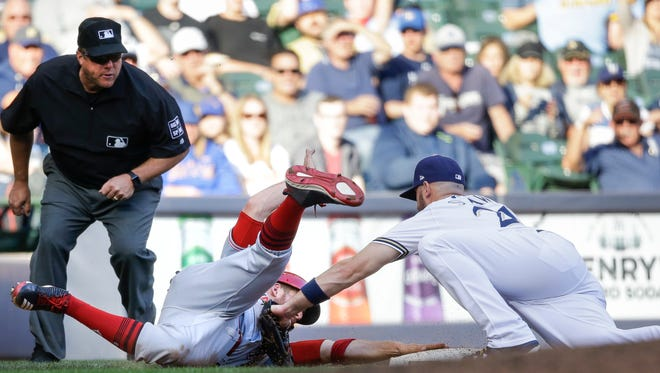 Milwaukee Brewers' Travis Shaw is late with the tag on Cincinnati Reds' Patrick Kivlehan, who was safe at third base during the sixth inning of a baseball game Thursday, Sept. 28, 2017, in Milwaukee.
