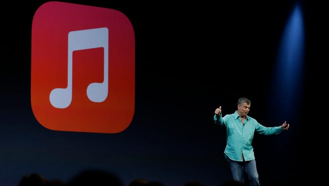 The iTunes logo is displayed during an Apple event in 2013.